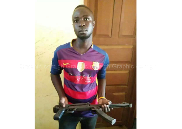 The suspect, Mensah Lare, holding the gun at the police station