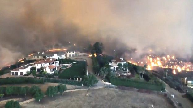 Aerial footage shows fires racing up hillsides in Malibu towards abandoned homes