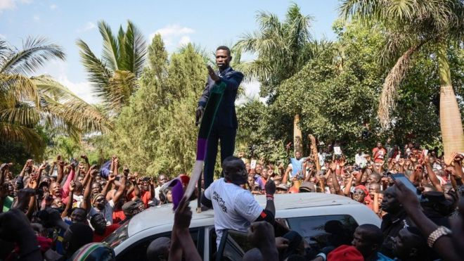 Bobi Wine spoke atop a vehicle to jubilant crowds outside his home