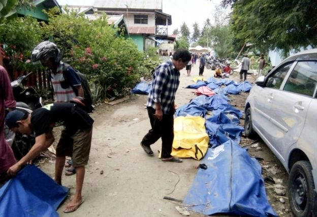 Locals check bodybags in the streets of Palu as they search for lost relatives
