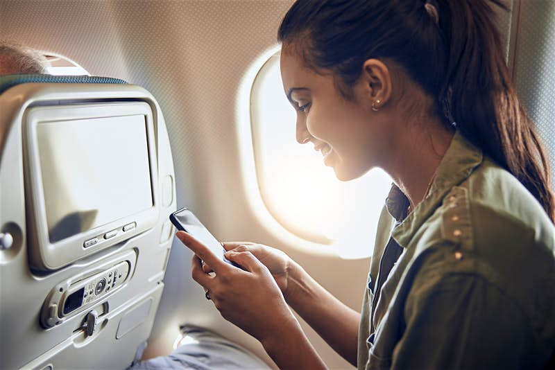 Travellers use their mobiles phones on flights © DaniloAndjus / Getty Images