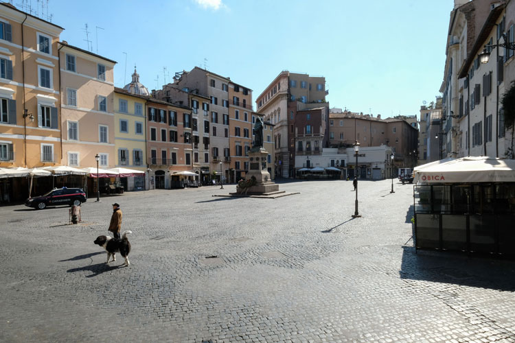 A man walks his dog across a deserted Piazza Campo dei Fiori in central Rome on March 24 during Italy's lockdown aimed at stopping the spread of the coronavirus pandemic. Andreas Solaro/AFP/Getty Images